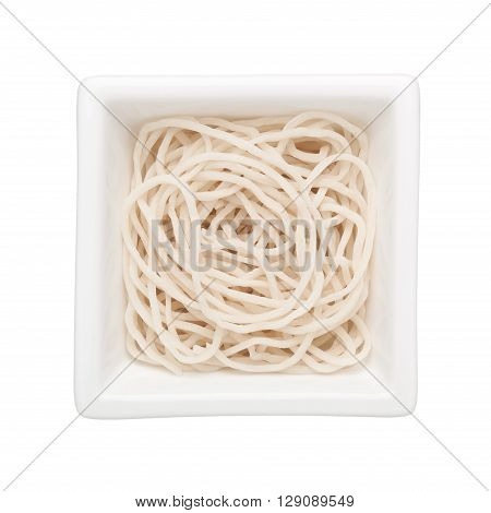 Uncooked noodles in a square bowl isolated on white background