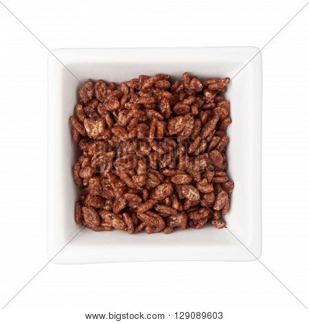 Chocolate flavored breakfast cereal in a square bowl isolated on white background