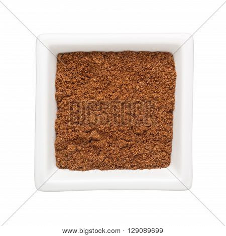 Coriander powder in a square bowl isolated on white background