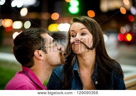 Couple having fun in street at night - making moustache with their hair