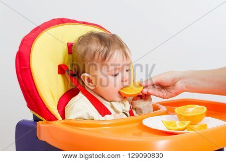 Baby Sits In  Highchair With Orange.