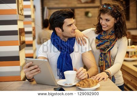 Young couple having breakfast in cafeteria, using tablet computer.