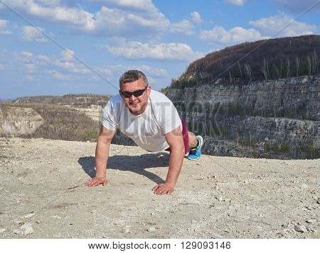 Man Doing Pushups Outdoors In Nature.