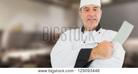 Portrait of a serious chef holding a knife against close up on a gas cooker