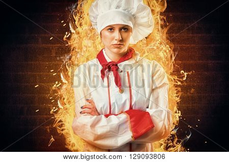 Pretty chef standing with arms crossed against red background