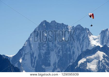 Paragliding flying over Mont Blanc Massif, in the background is Grandes Jorasses peak, Alps, Chamonix, France