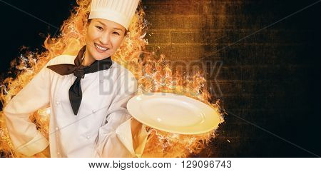 Smiling female cook holding empty plate in kitchen against dark wall