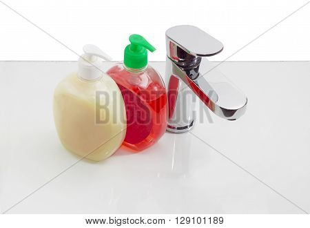 Single handle mixer and two plastic bottles of liquid soap on a reflective surface on a light background