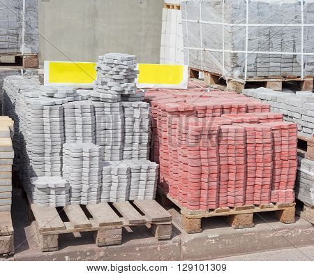 Red and gray concrete pavement tiles with ornament made by vibration casting method stacked on a pallet on a warehouse