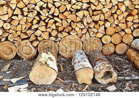 Closeup of pile of stacked round and triangle firewood in the yard prepared for fireplace and boiler.