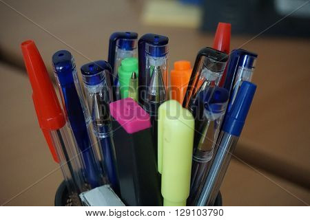 Typical colorful writing utensils in the business environment with ball pens, highlighters and pens