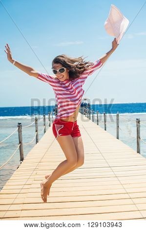young woman full of energy jumping on a pontoon in front of the sea on a sunny day.