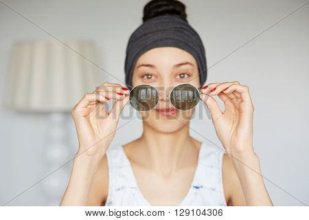 Selective Focus, Film Effect. Headshot Of Young Fashionable Woman Taking Off Her Trendy Hipster Roun