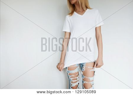 Close up indoor lifestyle portrait of beautiful young blonde woman standing against white wall looking away. Female in blank T-shirt and ripped jeans relaxing at home after hard working day