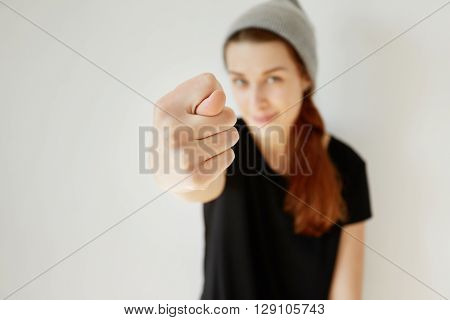 Close up of young stylish girl showing fig sign at the camera. Hipster female wearing gray cap and black T-shirt having fun making fig gesture posing isolated indoor.