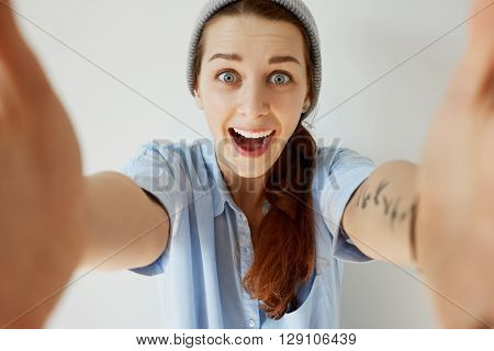 Portrait Of Young Redhead Woman Wearing Blue T-shirt Screaming With Excitement And Joy. Headshot Of