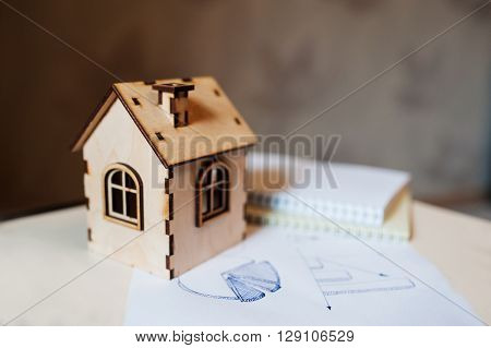Real estate concept wooden toy house with paper diagram.