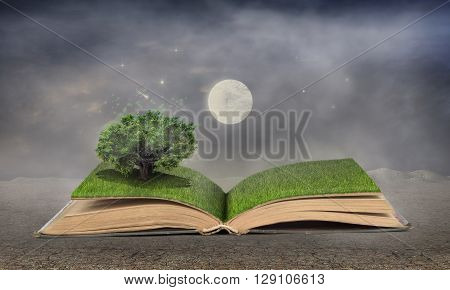 Concept of dreaming. Open book full of grass with a magical tree. Moon and stars at night. Concept of reading.