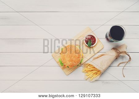 Burger, Chips and cola. Hamburger and french fries wrapped in brown wrapping paper. Fast food take away at white shabby chic wood. Hamburger with tomato sauce. Top view, flat lay with copyspace