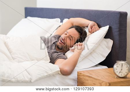 Young man stretching while waking up in the morning. Man yawning while waking up. Lazy young man in sleep. Portrait of latin man yawns and stretches in bed.