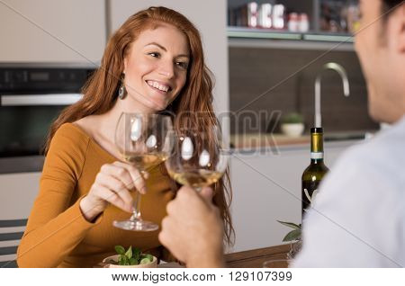 Young friend meeting after a long time. Young couple raising a toast with white wine at home. Happy couple having dinner at home and toasting with wine.