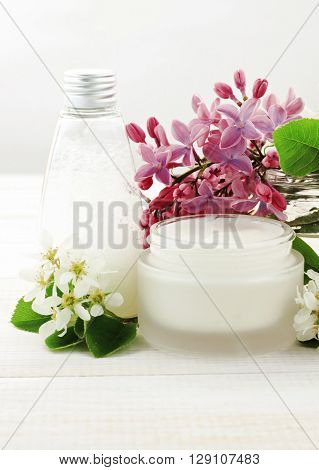 Holistic face and body cream, foamy cleanser toner, fresh flowers. White cosmetic products.