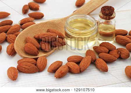 Sweet almond oil in bottles, almond kernels scattered.