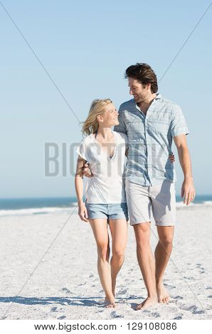 Front view of couple walking and looking at each other at beach. Couple in a bright sunny day walking at sea shore. Loving couple at beach strolling.