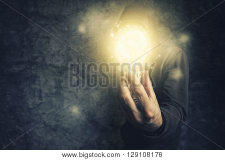 Hooded unidentifiable person holding light bulb as symbol of new ideas