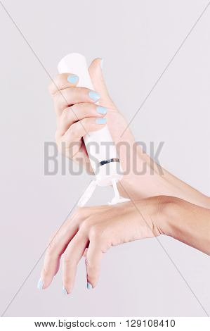 Young woman applying lotion on hands - close up