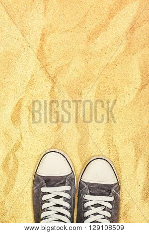 Sneakers on on warm sand top view of young man feet standing in desert.