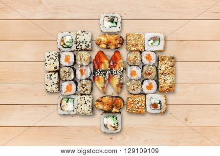 Japanese food restaurant, unagi sushi california roll plate or platter set. Sushi at wooden planks background. Top view, flat lay. Big party sushi set.