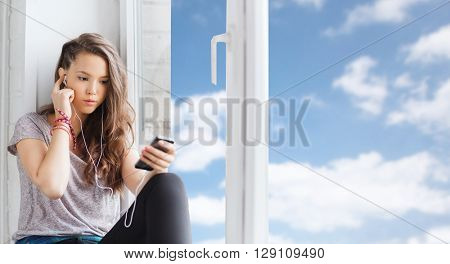people, technology and teens concept - sad pretty teenage girl sitting on windowsill with smartphone and earphones listening to music over blue sky and clouds background