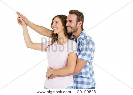 Happy young couple embracing and pointing upward on white background