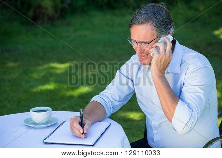 Casual businessman taking notes and having a phone call sitting on a terrace