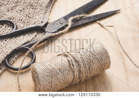 Old scissors and skein jute twine on a wooden background.