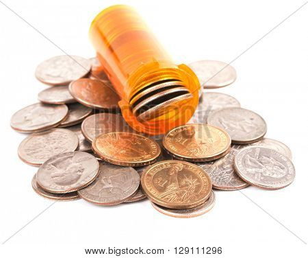 Medicine bottle filled with money, on top of a heap of quarters and dollar coins, concept of expensive medical care; on white