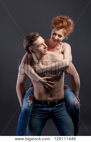 Loving couple posing at camera, on gray background
