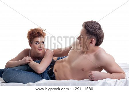 Red-haired girl and her sexy boyfriend posing in bed