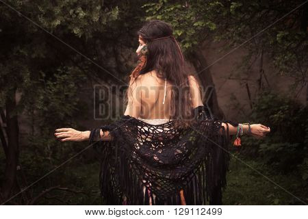 beautiful young woman in boho style clothes in garden summer day back view