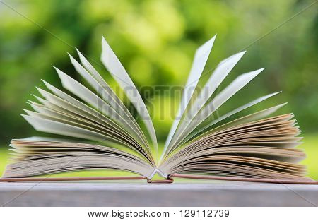 Open book on wooden table - outside shoot