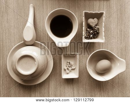 Flat lay of stylish dining set arrangement for shabu shabu with sauce and condiments, in sepia