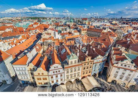 Cityscape of Prague, Czech Republic. View on traditional red roof tenement houses as seen from Old Town City Hall. Blue sunny sky, wide angle skyline