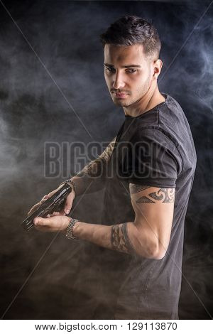 Young handsome man holding a hand gun, wearing black t-shirt, on dark background in studio