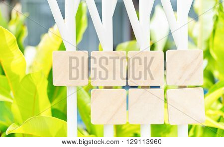blank sandstone sign plates hang on steel columns in green garden background. Ready to fill text and symbol