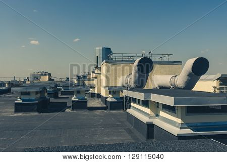 Pipes of ventilation are located on a wall of a residential building