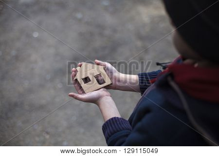 homeless boy holding a cardboard house dirty hand