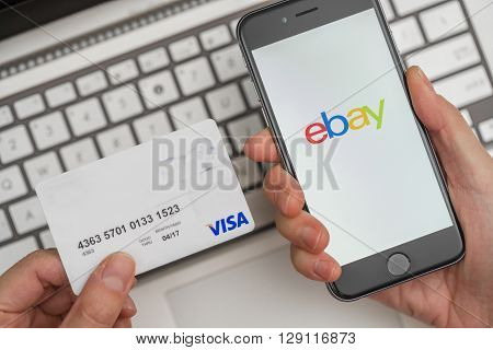 Melbourne, Australia - May 10, 2016: Using eBay app on iphone and credit card for online shopping. eBay is an online auction and shopping website.