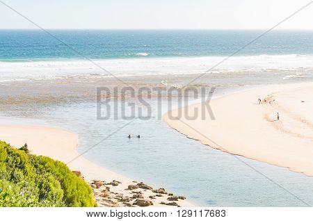 SEDGEFIELD SOUTH AFRICA - MARCH 4 2016: Holidaymakers at the mouth of the Swartvlei (Black Lake) the largest of the lakes in the Wilderness Lake Area