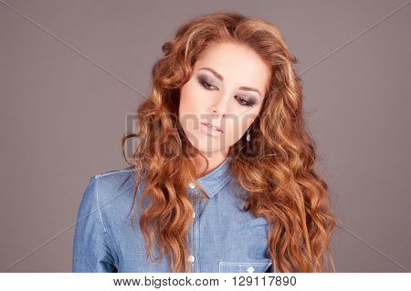 Beautiful girl with long ginger hair posing in room over grey. Wearing denim shirt. 20s. Looking down.